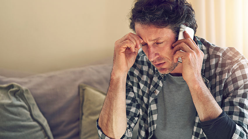 Man Answering a Fraudulent Phone Call